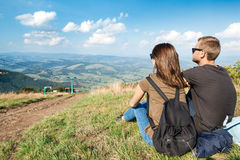 Young couple enjoying mountains landscape, sitting on hill back to camera. Young beautiful couple enjoying mountains landscape, sitting on hill back to camera Royalty Free Stock Photography