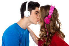 Young couple enjoying music and kissing Royalty Free Stock Image