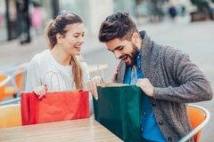 Young couple enjoying in outdoor cafe after shopping. Stock Images