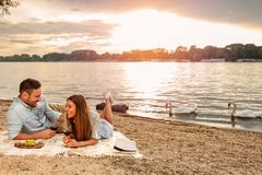 Young couple enjoying a picnic at the beach. Lying on the picnic blanket. White swans swimming the background royalty free stock images