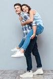 Young couple enjoying piggyback ride over gray background Royalty Free Stock Images