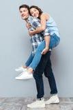 Young couple enjoying piggyback ride over gray background Stock Photos