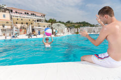 Young Couple Enjoying at the Pool with Beach Ball Royalty Free Stock Image