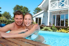 Young couple enjoying in private pool. Young couple in private swimming pool Royalty Free Stock Image