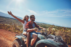 Young couple enjoying quad bike ride Stock Photo