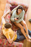 Young couple enjoying red wine on the couch. At home in the living room Royalty Free Stock Photos