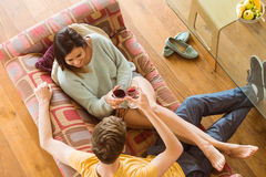 Young couple enjoying red wine on the couch Royalty Free Stock Images