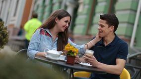 Young couple enjoying romantic date in street cafe stock footage