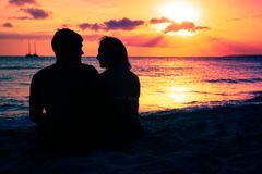 Young Couple Enjoying Sunset By The Beach. Young couple enjoying a romantic sunset by the beach Stock Photography