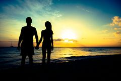 Young Couple Enjoying Sunset By The Beach. Young couple enjoying a romantic sunset by the beach Royalty Free Stock Image