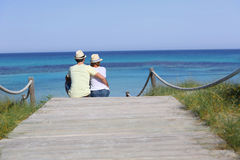 Young couple enjoying sitting by the beach. Back view of couple relaxing on beach pontoon Stock Photos