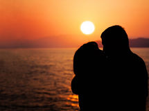Young Couple Enjoying the Sunset on the Beach. Kiss. Silhouette of Man and Woman stock image