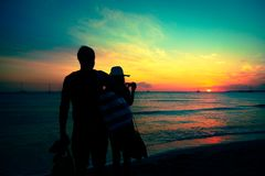 Young Couple Enjoying Sunset By The Beach. Young couple enjoying a romantic sunset by the beach Stock Photo