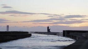 Young couple enjoying sunset at breakwater pier with lighthouse. stock video footage