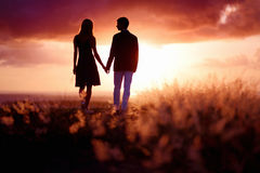 Young couple enjoying the sunset Stock Photos