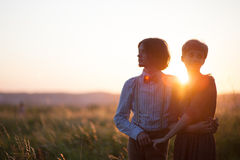 Young couple enjoying the sunset in the meadow Royalty Free Stock Photos