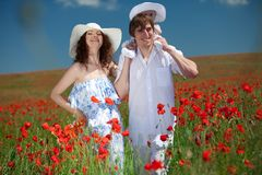 Young couple and their baby-girl in poppy field royalty free stock image