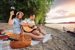 Young couple enjoying their time, having romantic picnic at the beach. Playing guitar and singing stock photo