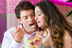 Young couple enjoying their time in ice cream parlor Stock Photos