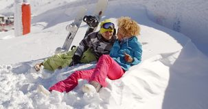 Young couple enjoying their winter vacation. Lying side by side in fresh white snow in the sunshine with their snowboards smiling at the camera stock video footage