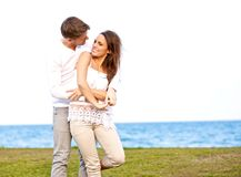 Young Couple Enjoying Themselves by the Beach. Portrait of a romantic young couple enjoying themselves by the beach Stock Photos
