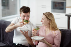 Young couple enjoying themselves and eating pizza Stock Photos