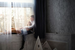 Young couple enjoying themselves on the windowsill Royalty Free Stock Photos