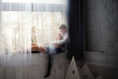 Young couple enjoying themselves on the windowsill Stock Photography