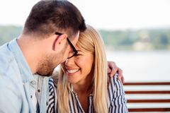 Young couple hugging and touching with foreheads. Relaxing in a cafe royalty free stock photo