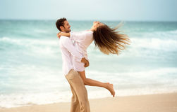 Young couple enjoying together on beach. Young men spinning his girl in a circle Stock Photography