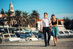 Young couple enjoying vacation time.Boyfriend and girlfriend having a romantic walk along the coast in a seaside town. Romantic weekend at he coastal city Royalty Free Stock Photos