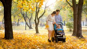 Beautiful young couple enjoying walking at autumn park with their 1 year old baby boy sitting in buggy. Young couple enjoying walking at autumn park with their 1 Royalty Free Stock Photo