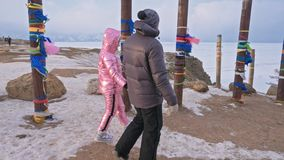 Young couple enjoying walking outdoors in winter top mountains. Buddhist Ritual poles with colored ribbons in the winter. At the holy site of Lake Baikal stock footage