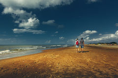 Young Couple Enjoyng Walking Along Sandy Shore, Rear View. Walking Hiking Journey Together Concept Royalty Free Stock Photo