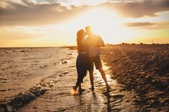 A young couple enjoys a mid summer late afternoon, on a wet san stock image