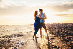 A young couple enjoys a mid summer late afternoon, on a wet san stock images