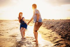 A young couple enjoys a mid summer late afternoon, on a wet san royalty free stock image