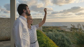 Young couple enjoys the view of the ocean stock video footage