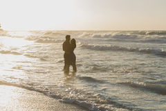 Young couple enjoys walking on a hazy beach at. Barefoot young couple, the women in a blue dress, and the men in shorts, enjoys a romantic walk on a sandy beach Royalty Free Stock Image