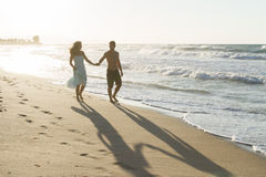 Young couple enjoys walking on a hazy beach at Royalty Free Stock Photos