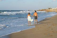 Young couple enjoys walking on a hazy beach at dusk. Stock Photography