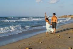 Young couple enjoys walking on a hazy beach at dusk. Royalty Free Stock Photos