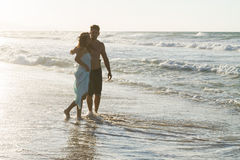 Young couple enjoys walking on a hazy beach at dusk. Royalty Free Stock Photo