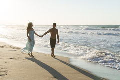 Young couple enjoys walking on a hazy beach at dusk. Royalty Free Stock Photography
