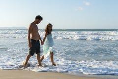 Young couple enjoys walking on a hazy beach at dusk. Stock Photos