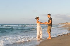 Young couple enjoys walking on a hazy beach at Stock Photo