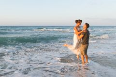 Young couple enjoys walking on a hazy beach at Royalty Free Stock Photo