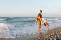 Young couple enjoys walking on a hazy beach at Royalty Free Stock Photography