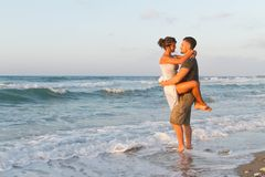 Young couple enjoys walking on a hazy beach at. Loving young couple at the beach , in a late summer hazy day at dusk, wearing  a white dress and shorts, enjoying Stock Images