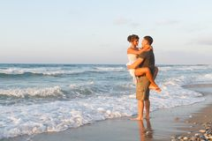 Young couple enjoys walking on a hazy beach at. Loving young couple at the beach , in a late summer hazy day at dusk, wearing  a white dress and shorts, enjoying Royalty Free Stock Photos